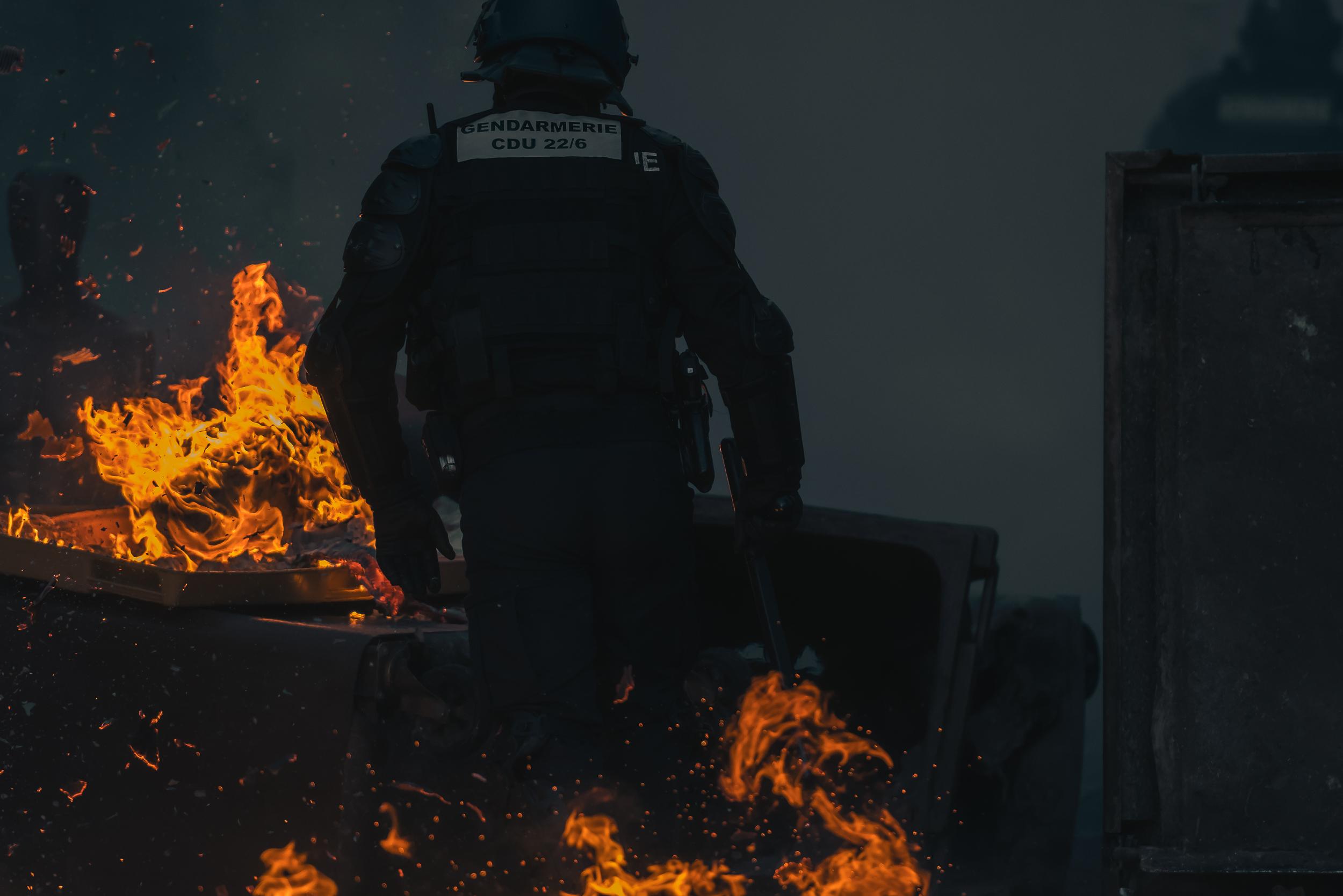 Un gendarme déblaie une poubelle en feu.